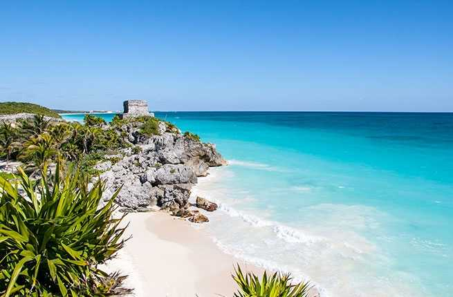 A view of the sugary beach and clear, blue water in Tulum